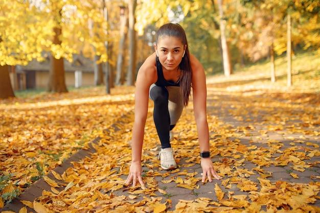 Chica deportiva en un top negro entrenamiento en un parque de otoño Foto gratis