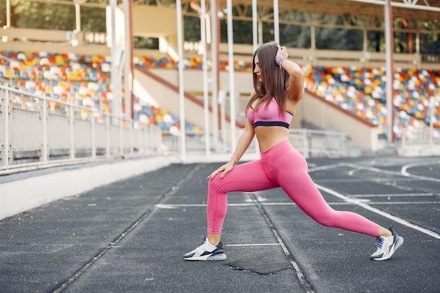 Chica deportiva en un uniforme rosa entrenamiento en el estadio Foto gratis
