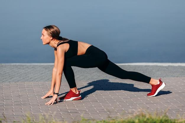 Chica deportiva warmimg al aire libre y estirando las piernas. vista lateral- Foto Premium