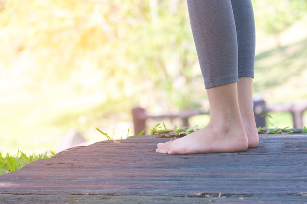 Chica descalza de pie en el camino a pie en el parque Foto Premium