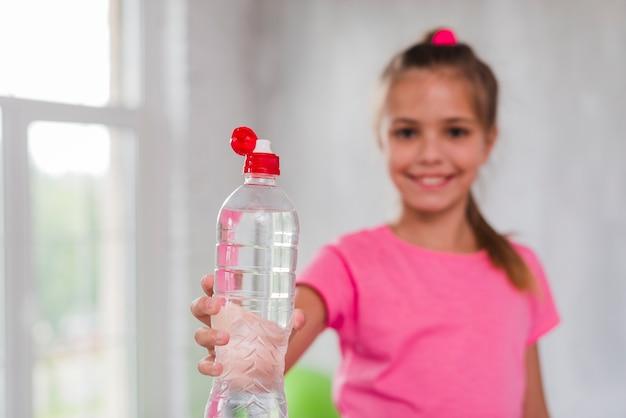 Chica desenfocada dando plástico botella de agua hacia la cámara Foto gratis