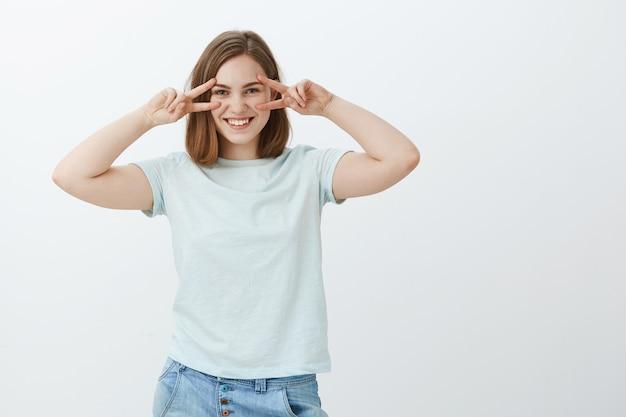 Chica disfrutando de la juventud. encantadora mujer europea joven de aspecto amistoso en camiseta casual que muestra paz o gestos disco sobre los ojos que se sienten juguetones y entretenidos colgando contra la pared gris Foto gratis