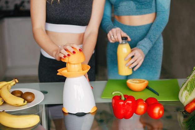 Chica de dos deportes en una cocina con verduras Foto gratis