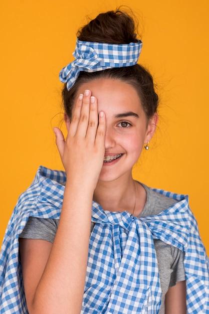 Chica elegante cubriendo un ojo Foto gratis