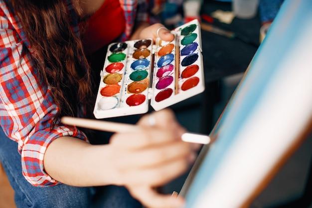 Chica elegante dibuja en un estudio de arte. Foto gratis