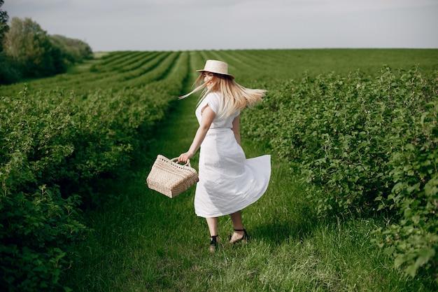 Chica elegante y con estilo en un campo de verano Foto gratis