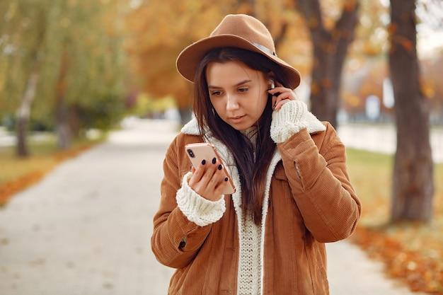 Chica elegante y con estilo en un parque de otoño Foto gratis