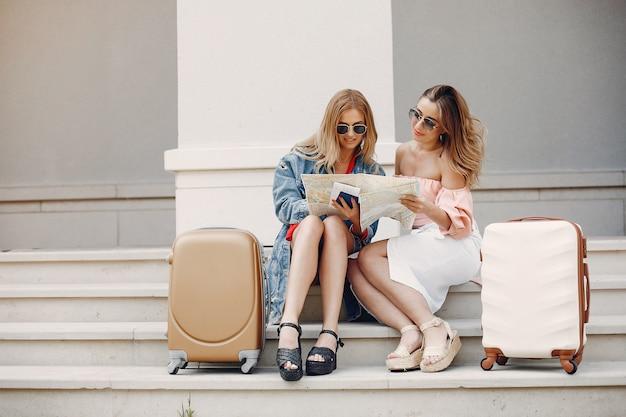 Chica elegante y con estilo sentada con una maleta Foto gratis