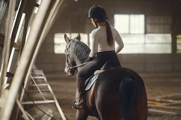 Chica elegante en una granja con un caballo Foto gratis
