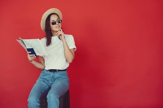 Chica elegante posando con equipo de viaje en una pared roja Foto gratis