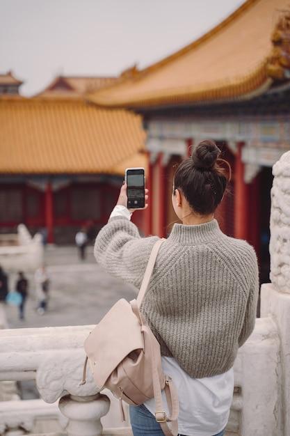 Chica elegante visitando la ciudad prohibida en beijing, china Foto gratis