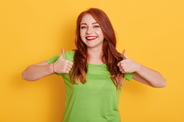 Chica encantadora alegre mostrando los pulgares para arriba mientras posa aislada, chica pelirroja en camiseta verde Foto gratis
