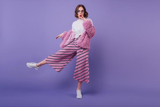 Chica encantadora sorprendida en zapatos blancos posando en la pared púrpura durante la sesión de fotos en interiores. retrato de cuerpo entero de mujer rizada interesada en pantalón rosa y elegante chaqueta de piel. Foto gratis