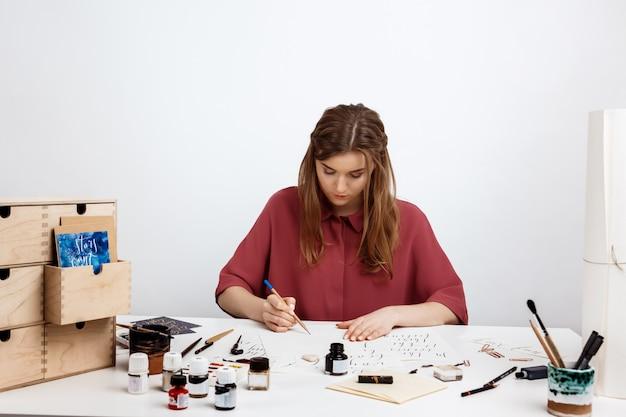 Chica escribiendo caligrafía en postales. diseño artístico. Foto gratis