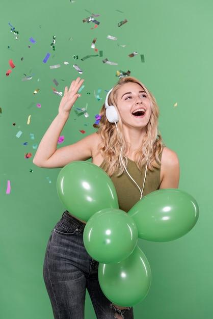 Chica escuchando música y sosteniendo globos Foto gratis