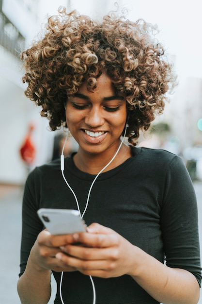Chica escuchando música desde su teléfono. Foto gratis