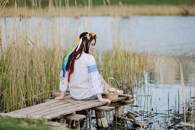 Chica eslava en camisa ucraniana sentada en el puente con pascua Foto Premium