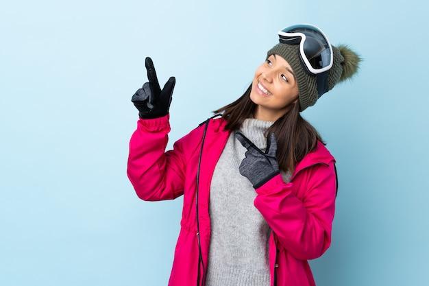 Chica de esquiador de raza mixta con gafas de snowboard en azul aislado señalando con el dedo índice una gran idea Foto Premium