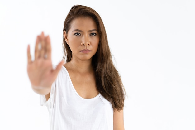 Chica estricta mostrando señal de stop Foto gratis