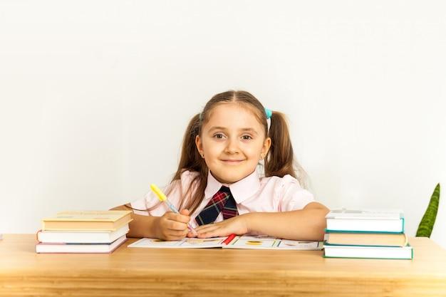 Chica estudiando en la mesa sobre fondo blanco. Foto Premium
