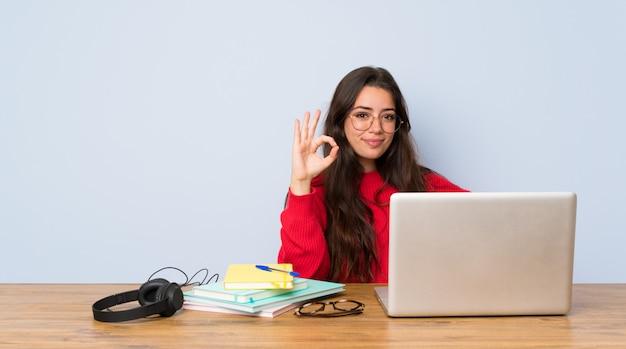 Chica estudiante adolescente estudiando en una mesa que muestra signo bien con los dedos Foto Premium