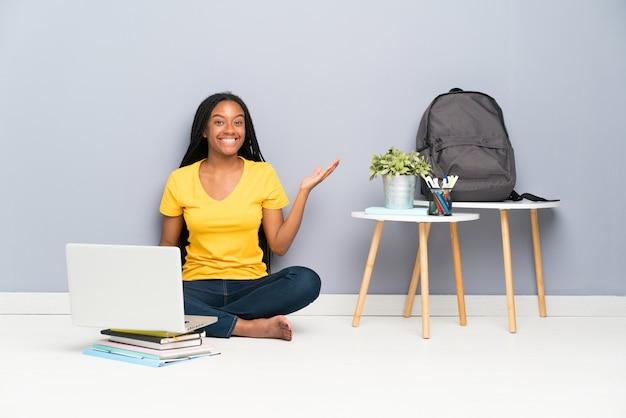Chica estudiante adolescente sentada en el suelo sosteniendo copyspace imaginario en la palma Foto Premium