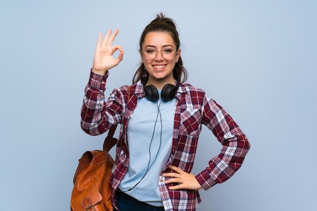 Chica estudiante adolescente sobre pared azul aislada mostrando signo bien con los dedos Foto Premium