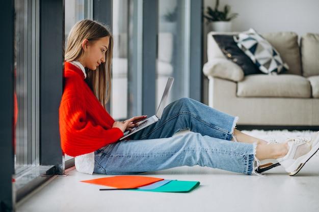 Chica estudiante estudiando en la computadora junto a la ventana Foto gratis