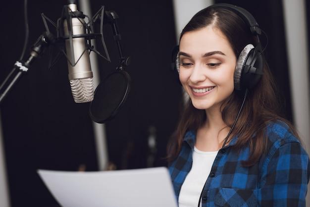 La chica en el estudio de grabación canta una canción. Foto Premium