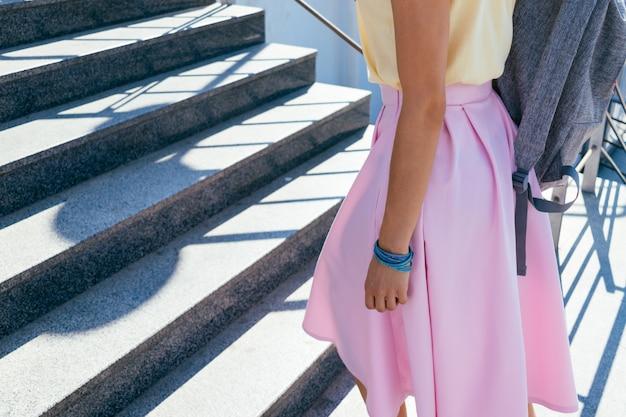 Chica en falda rosa y camiseta amarilla subiendo escaleras al aire libre Foto Premium