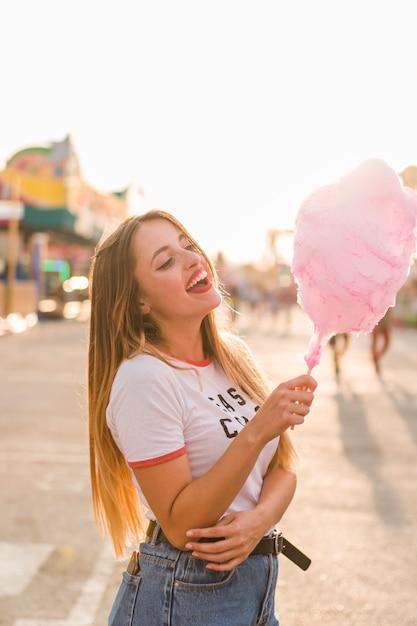 Chica feliz comiendo algodón de azúcar Foto gratis