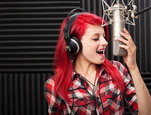 Chica feliz grabando una canción Foto gratis