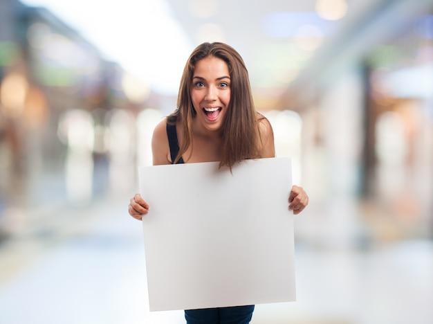 Chica feliz sosteniendo un cartel en blanco Foto gratis