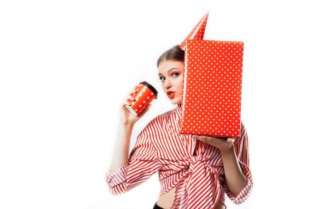Chica en una fiesta en una camisa a rayas rojas con regalos en blanco Foto Premium