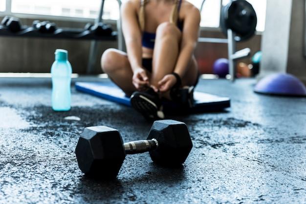 Chica fitness atándose los cordones Foto gratis