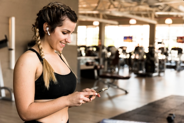 Chica fitness usando su móvil Foto gratis