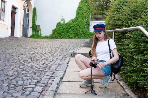 La chica fotógrafa se prepara para tomar fotos en la calle. Foto Premium