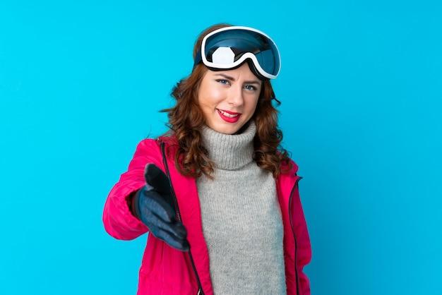 Chica con gafas de nieve sobre pared aislada Foto Premium