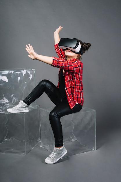 Chica con gafas de realidad virtual tocando sus manos en el aire Foto gratis