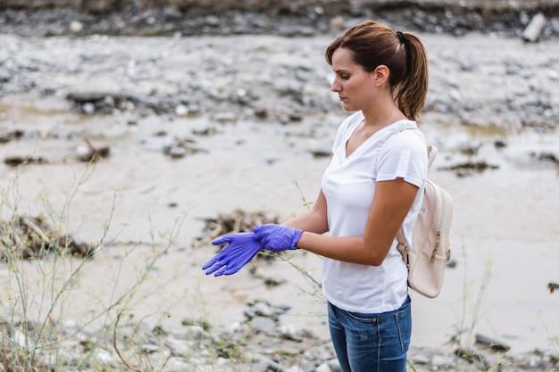 Chica con guantes azules con un río en el Foto Premium