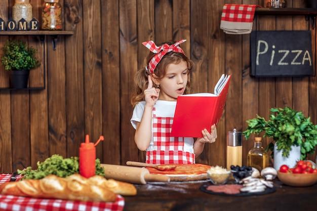 Chica guapa en delantal a cuadros leyendo el libro de recetas Foto Premium