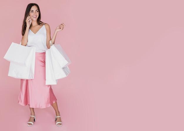 Chica guapa con muchas bolsas de compras sobre fondo rosa Foto gratis