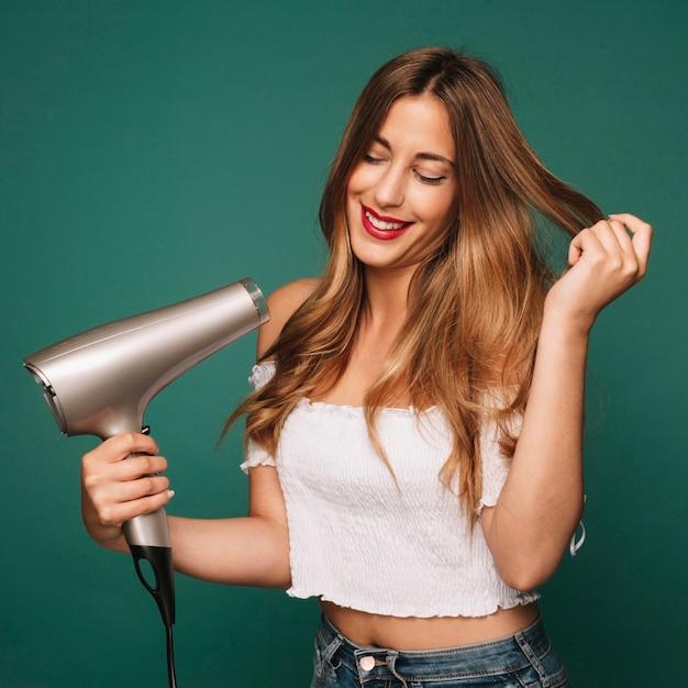 Chica guapa con secador de pelo Foto gratis