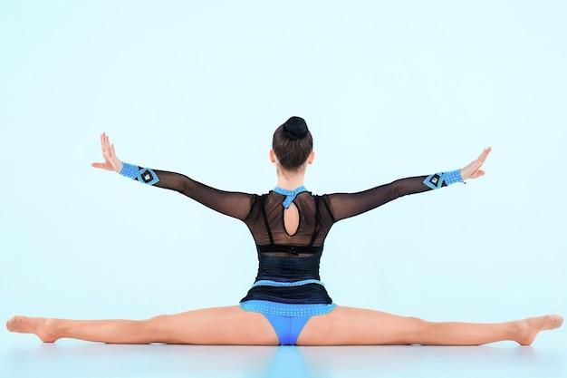 La chica haciendo gimnasia baila en un espacio azul Foto gratis