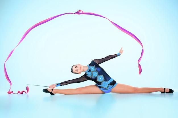 La chica haciendo gimnasia danza con cinta de color en un espacio azul Foto gratis
