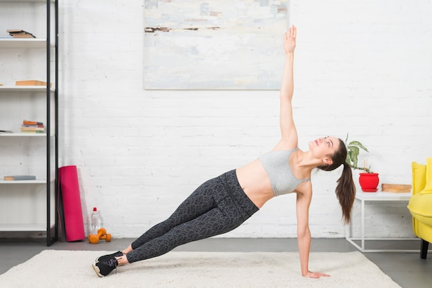 Chica haciendo yoga en su casa Foto gratis