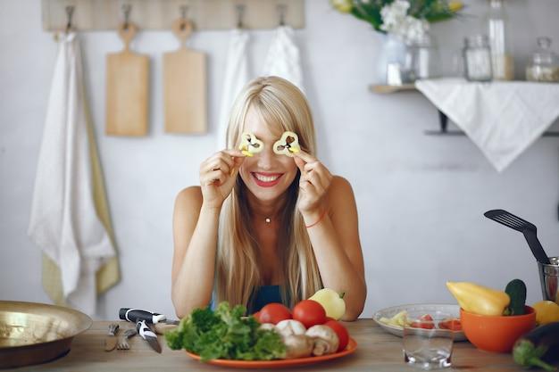 Chica hermosa y deportiva en una cocina con verduras Foto gratis