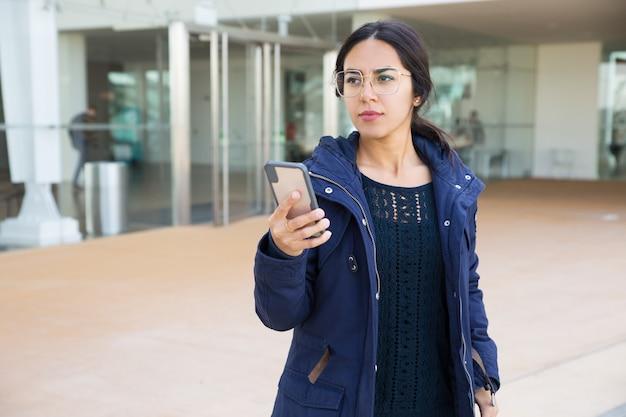 Chica hermosa seria que usa la aplicación móvil Foto gratis