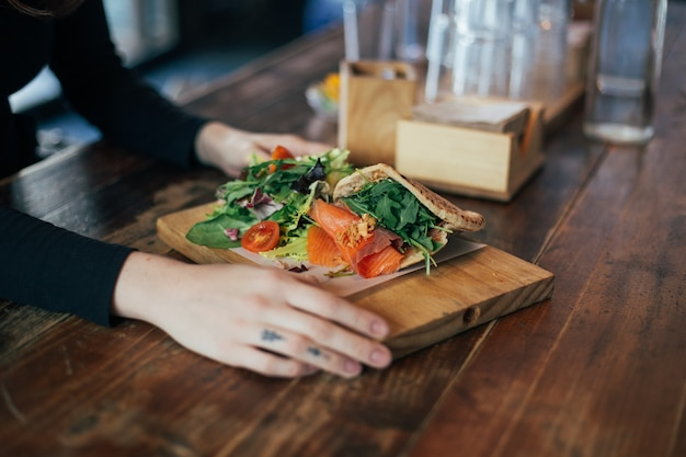 Chica hipster come sándwich de salmón en pita griego Foto gratis