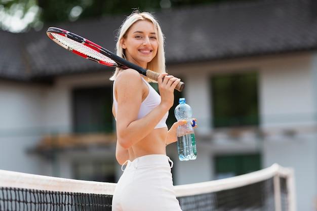 Chica joven activa que sostiene la botella de agua Foto gratis
